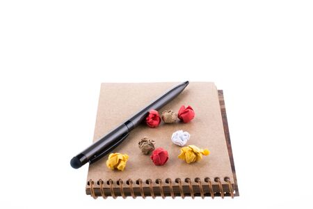spiral notebook: Crumpled paper and pollpoint pen on a spiral notebook on white background