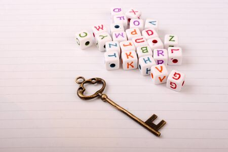 conceptional: A beautiful metal key and cube letters of alphabet side by side on a sheet of paper