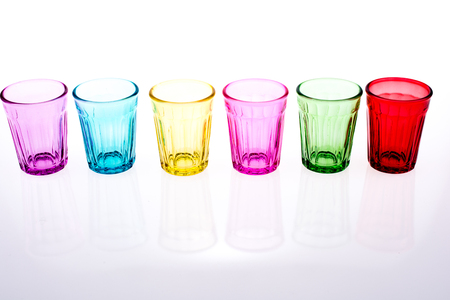 lined up: Colorful drinking glass lined up on white background