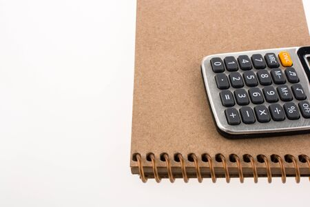 spiral notebook: Calculator and a spiral notebook on white background Stock Photo