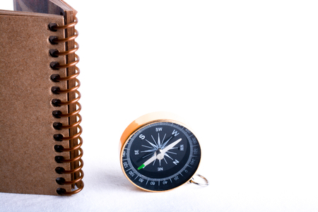 conceptional: Compass by the side of a  spiral notebook on a white background Stock Photo