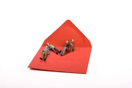 conceptional: Figurine men out of an envelope on white background Stock Photo