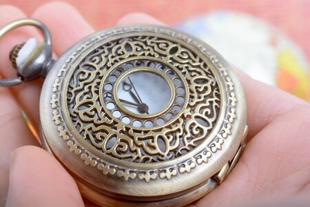 retro styled: Man holding a retro styled Pocket watch in hand
