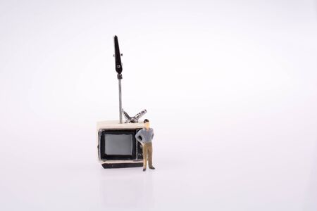 retro styled: Man standing by a retro styled television set on a white background