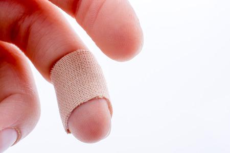 herida: el dedo en el vendaje blanco sobre un fondo blanco