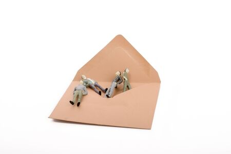 chap: Figurine men out of an envelope on white background Stock Photo