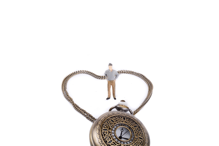 retro styled: Retro styled pocket watch and its chain form a heart and a little figurine stands in it