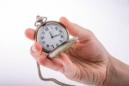 Mano que sostiene un reloj de bolsillo de estilo retro en la mano