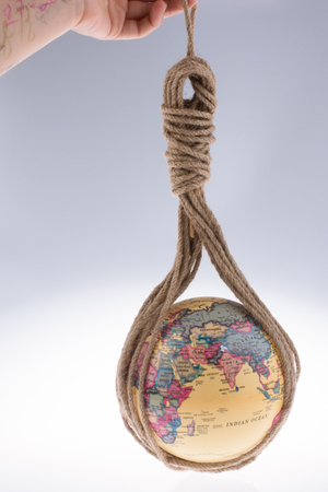 the meridian: globe hanging in rope on white background Stock Photo