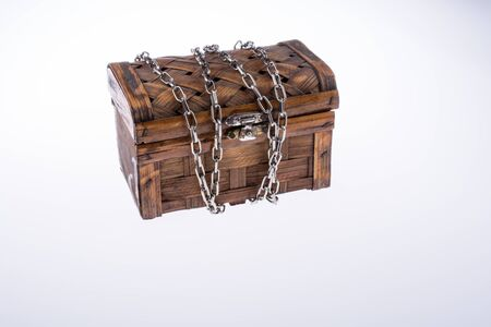 coffer: Wooden brown treasure box in chains on a white background