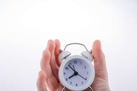 conceptional: Alarm clock in hand on a white background Stock Photo