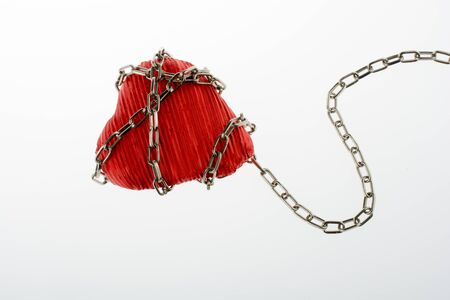 forbidden love: Red color heart shaped object in Chain on white background