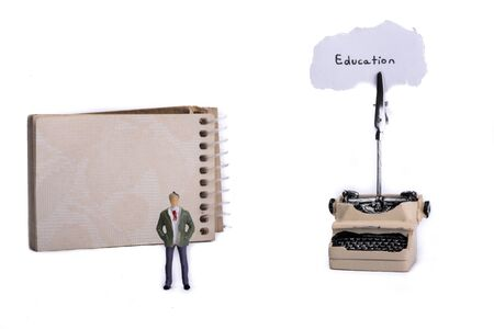 spiral notebook: Man standing in front of a typewriter and a spiral notebook on a white background