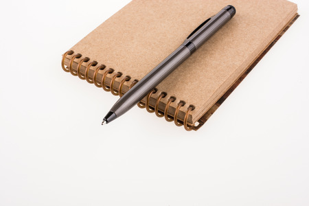 spiral notebook: Spiral notebook and pollpoint pen on a white background