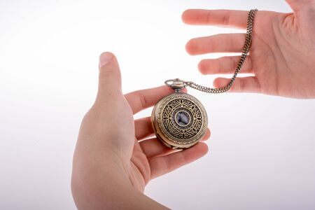 hand in pocket: Hand holding a retro styled pocket watch in hand Stock Photo