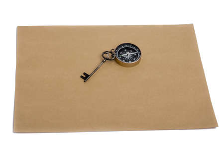 conceptional: key and compass on a sheet of colored plain paper with a white background