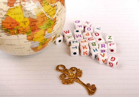 conceptional: Globe, key and cube letters of alphabet side by side on a white paper Stock Photo