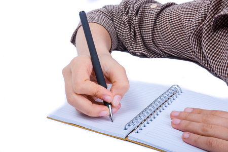 A child hand is writing with pen on a spiral notebook on white background Banco de Imagens