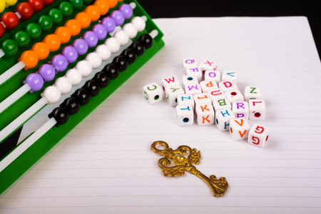 conceptional: Abacus, key and cube letters of alphabet side by side on  white paper Stock Photo