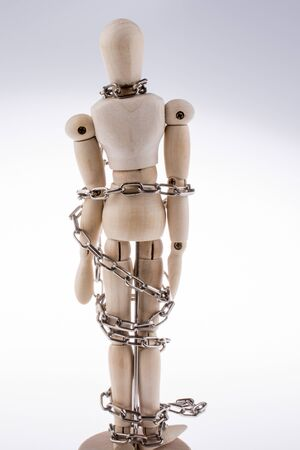 chaining: Wooden model man in chains on a white background