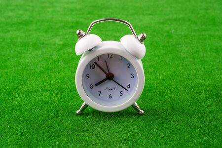 clockwise: Retro clock on green grass Stock Photo
