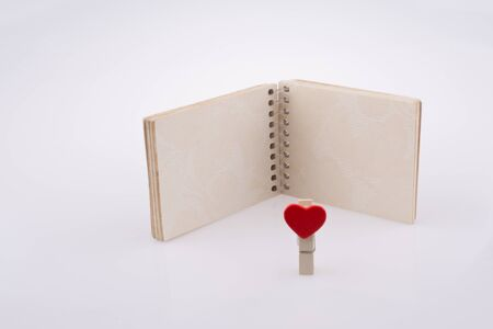 hearted: Red hearted clip nearby a notebook