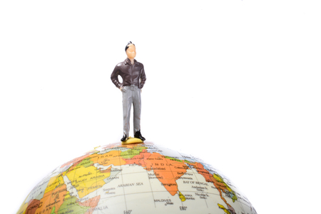 geosphere: Man figurine standing at the top of a globe on a white background