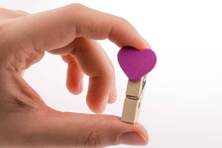 dearest: Hand holding a red clothespin with a heartshape on a white background