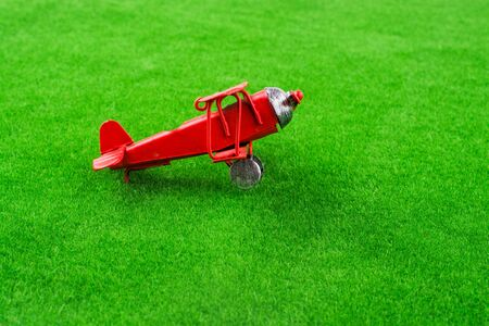 model airplane: Red little retro model airplane in green grass