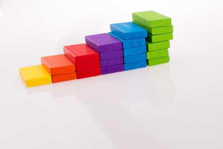multi color domino forming stairs on white background Stock Photo