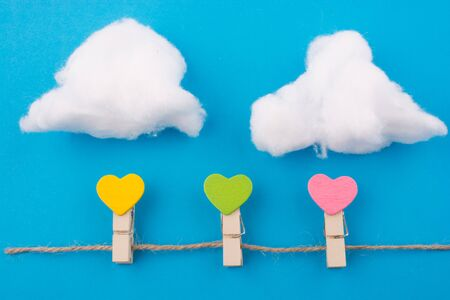 hearted: Colorful hearted clips with clouds on a blue background Stock Photo