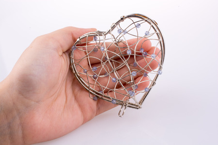Hand holding Heart cage on a background