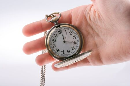 retro styled: Hand holding a retro styled pocket watch in hand Stock Photo