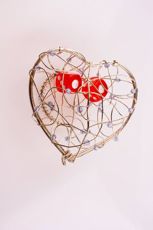 Red dice in a heart shaped cage on a white background Stock Photo