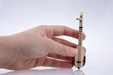 saz: Hand holding turkish musical instrument saz on a white background Stock Photo