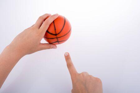 Hand holding an orange basketball model on a white background Imagens