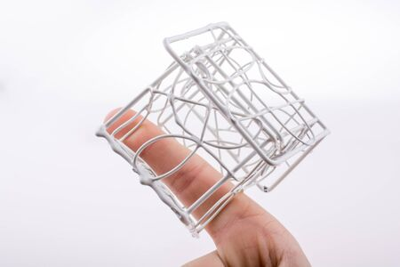 homeowners: Little  model house made of white metal wire in hand Stock Photo
