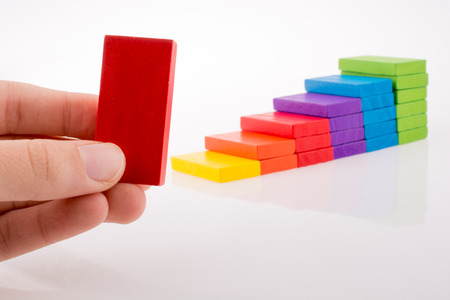 Hand spelen met gekleurde domino op een witte achtergrond