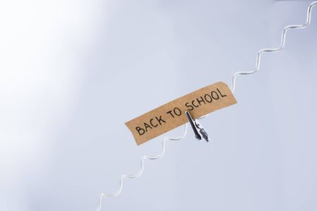 Back to school written on a note paper on white bakcground Stock Photo