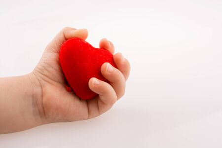 dearest: Little red color heart shape in hand on white background
