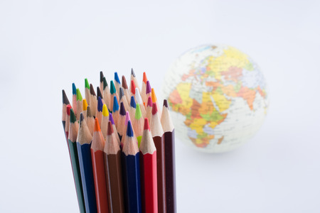 Color pencils of various color and globe on white background