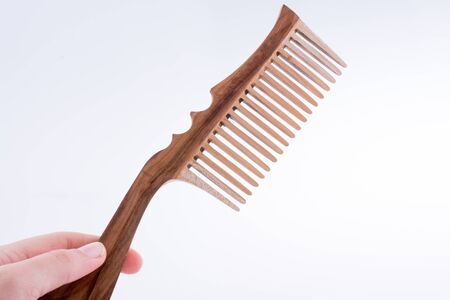 Hand holding a wooden hair comb on a white background Stock Photo