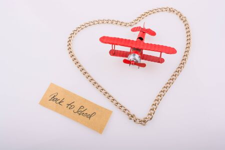 dearest: Chain forms a heart shape with a title back to school in it with a red model airplane