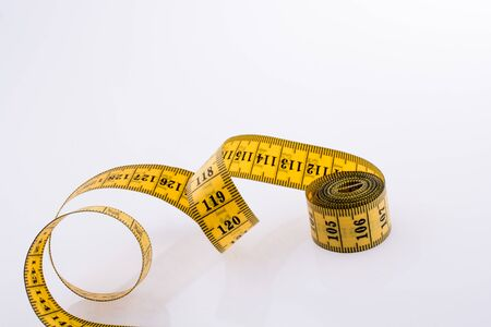 Yellow color measuring tape on a white background