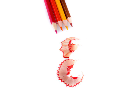 sharpenings: color pencils with its shavings on white background