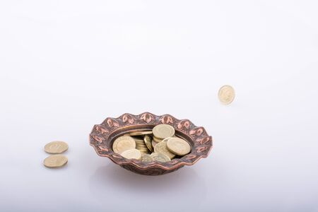 Coins inside and around a metal bowl