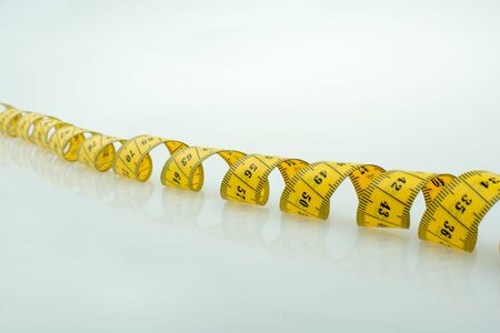Yellow measuring tape on a white background Stock Photo