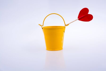 Little red color heart shape and yellow color bucket Stock Photo