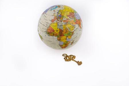 Retro styled key  by the globe on white background Stock Photo