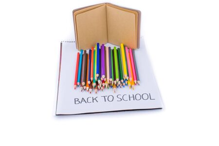 pedagogy: Color pencils, back to school title and a notebook Stock Photo